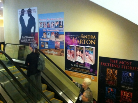 Wall-size posters over escalators, including m/m clinch cover.