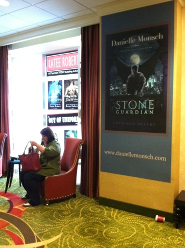 Lobby area wall and window posters, floor to ceiling, with fantasy and suspense book covers, looming over conference attendee seated in armchair.
