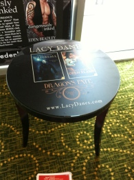 Occasional table in lobby area, with laminated image of Lacy Danes book covers; images of fantasy heroes with tattoos and leather jackets