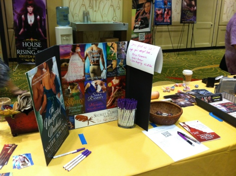 Table-top tri-fold display of Regency book covers, with promo swag including pens and bookmarks.