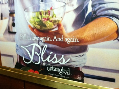 Another elevator wall poster, with torso of casually dressed white man holding a clear glass salad bowl and preparing and/or offering the salad.