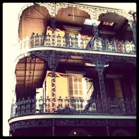 Corner of building in New Orleans with elaborate ironwork balconies, a photo I took in the French Quarter.