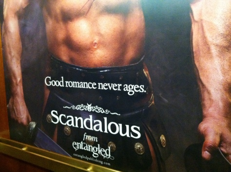 "Very large (over life size) poster covering rear wall of elevator; depicts a bare-chested white man in a kilt with the tagline ""good romance never ages"""